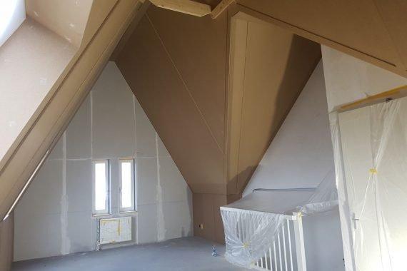 Zolder met bruine dak en vezelplaten voor het latexspuiten