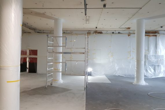 Wanden afdekken voor het latex spuiten van de plafonds in de kleur zwart