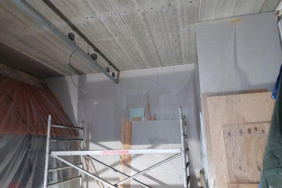 Onbehandelde plafond en leidingen voor het latex spuitwerk