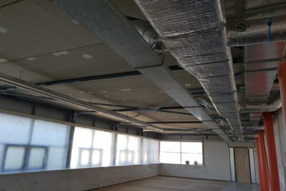 Betonnen plafonds, kabelgoten en luchtbehandelingskanalen voor het latex spuiten
