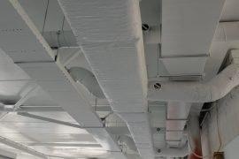 Betonnen plafonds, kabelgoten en luchtbehandelingskanalen na het latex spuiten